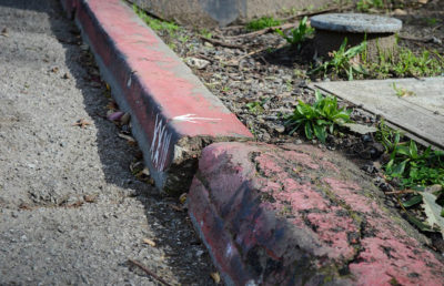 Crub on a sidewalk that is painted in red but its conditions are deteriorated as its paint is old, worn, and chipping.