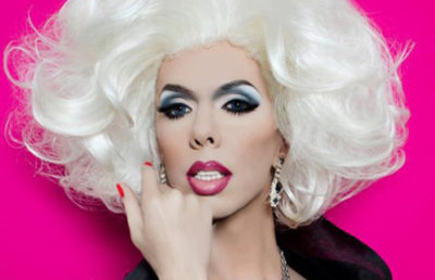 A person dressed in drag looks into the camera.