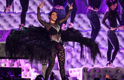 Woman performs on stage in a black costume with her hands up in the air.