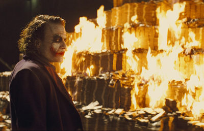 A man in messsy clown mackup stars at a burning money pile.