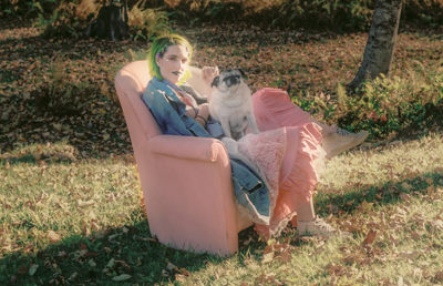 Person with green hair and a puffy pink skirt captivatingly gazes into the camera while sitting on a pink couch in the forest and a dog sits on their lap.