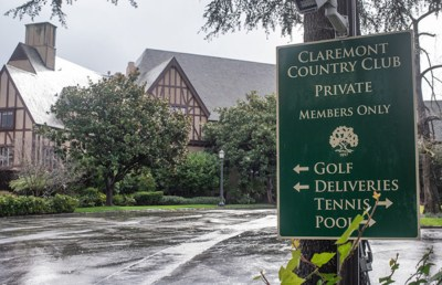"""A green sign reads """"Claremont Country Club"""" in front of a brown wooden building with many trees."""