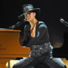 A woman dressed in a black long sleeve shirt, rhinestone covered pants, and a black hat performs before a microphone and piano.
