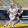 A lacrosse player runs on the field with her stick in hand as an opponent runs behind her.