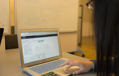 A person navigates the Cal Central webpage on their laptop.