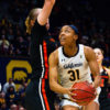 A basketball player holds the ball in her hand and looks up at an opponent who jump in front of her with her arms up.