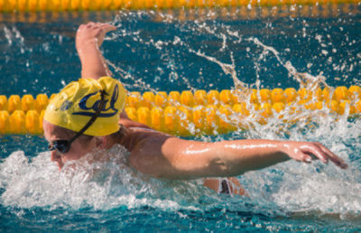 Swimmer has arms up in the air, propelling her forward in the water.