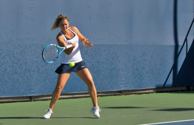 Tennis player strikes ball with racket.
