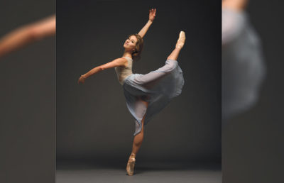 A dancer poses with a leg and an arm in the air while on her tippie toe.