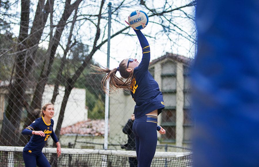 Volleyball player spikes the ball over the net.