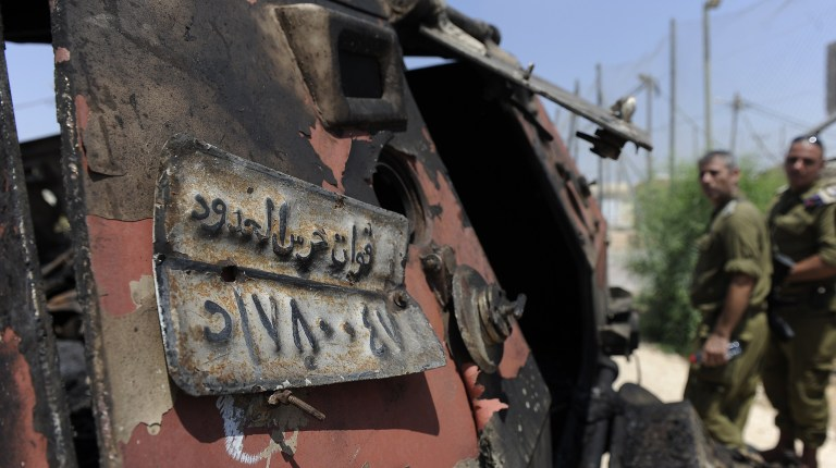 Israeli soldiers inspect a burnt armoured vehicle near the Kerem Shalom border crossing after unidentified gunmen crossed into Israel from Egypt on 6 August. The number plate reads 'Border Guards Forces' AFP PHOTO/DAVID BUIMOVITCH