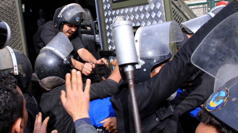 Security forces pull an arrested man into the back of a police van near Tahrir Square. (DNE/ Mohamed Omar)