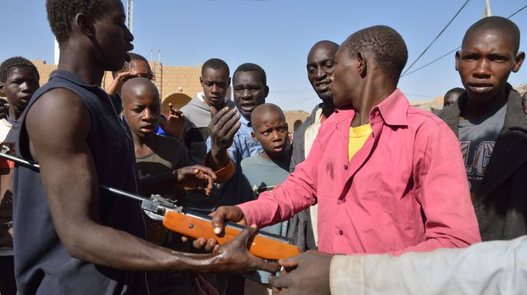 Men fight for an air rifle they just stole from a store of Timbuktu on January 29, 2013.  AFP/PHOTO ERIC FEFERBERG