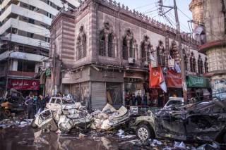 Warga Mesir menyaksikan puing-puing akibat ledakan bom mobil di depan kantor polisi di Kota Mansura, utara Kairo, Selasa (24/12/2013). Foto: MAHMOUD KHALED/afp