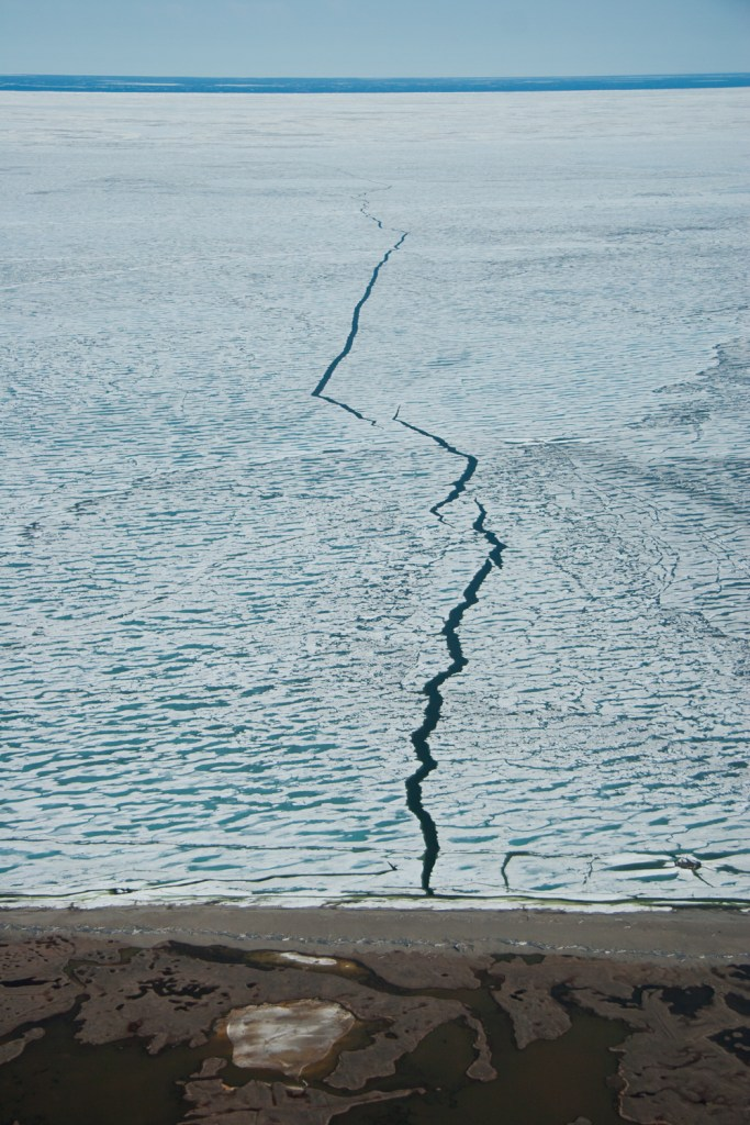 A crack in shore-fast sea ice with open water beyond in June, off the coast of the Arctic National Wildlife Refuge.