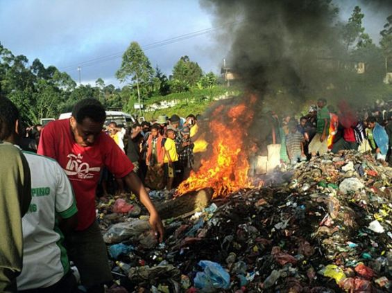 In this Wednesday, Feb. 6, 2013 photo, bystanders watch as a woman accused of witchcraft is burned alive in the Western Highlands provincial capital of Mount Hagen in Papua New Guinea. The 20-year-old mother of one, Kepari Leniata was stripped naked by several assailants, tortured with a hot iron rod, bound, doused in gasoline, then set alight on a pile of car tires and trash. PAPUA NEW GUINEA OUT Photo: Post Courier