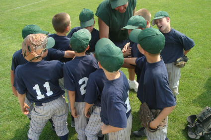 A youth baseball team prepares for a game n a huddle.  All hand in for a cheer.  Green and blue uniforms.