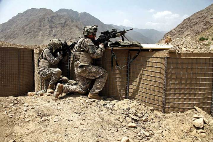 U.S. Army soldiers from 1st Battalion, 32nd Infantry Regiment man a firing position during a firefight at Vehicle Patrol Base Badel, Konar province, Afghanistan, Aug. 14, 2009. The soldiers quickly suppressed the enemy after receiving sniper fire from a nearby ridge line. U.S. Army photo by Staff Sgt. Andrew Smith