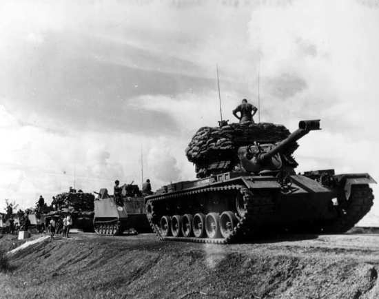 An M48 Patton gets ready to lead a convoy in South Vietnam. Notice that the M48 is modified with sandbags to add a pillbox-like quality to the tank. U.S. Army photo