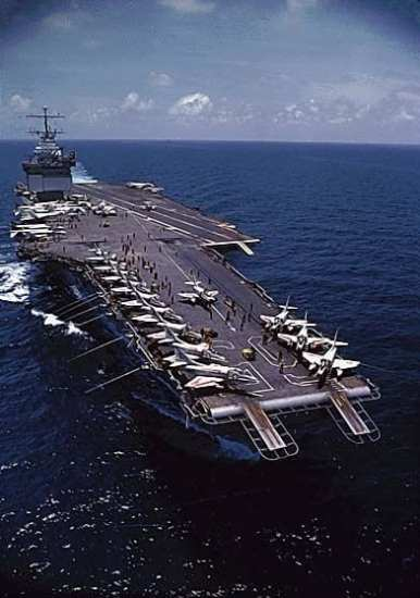 The nuclear powered aircraft carrier USS Enterprise (CVAN-65) cruises in the clear blue water of the Gulf of Tonkin off the shores of Vietnam. The aircraft on the flight deck belong to Carrier Air Wing Nine (CVW-9), tailcode NG. Visible are about 15 Douglas A-4C Skyhawk (mostly parked on the bow). Four McDonnell Douglas F-4B Phantom II fighters are parked next to the island, another one on the aft port flight deck. Next to the island two North American RA-5C Vigilante reconnaissance planes are visible. The large radome belongs to a Grumman E-1B Tracer AEW aircraft. The tail of a Douglas A-3B Skywarrior bomber is barely visible behind the island. The photo may have been taken out of the window of one of CVW-9's Kaman UH-2 Seasprite plane-guard helicopters. DOD photo