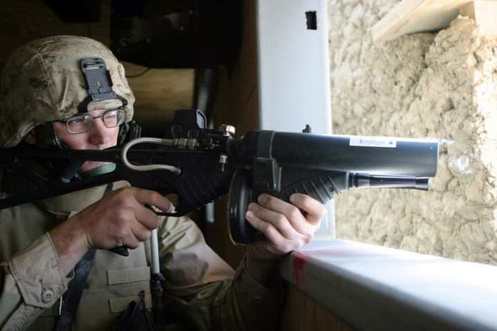U.S. Marine Corps Cpl. Luke Schemenauer, assigned to Headquarters Company, 6th Marine Regiment, fires a .68 caliber FN 303 Less Lethal System launcher during a training exercise inside the Military Operations in Urban Terrain (MOUT) facility at Bagram Air Base, Afghanistan. DoD photo by Lance Cpl. James P. Douglas, USMC.