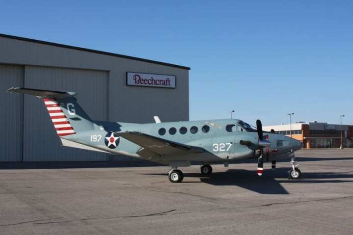 """A Hawker Beechcraft TC-12B training aircraft painted in vintage colors to celebrate the centennial of naval aviation. The paint scheme replicates that of U.S. Navy aircraft prior to May 15, 1942. After that date, the red and white rudder striping and red disc in the center of the white star were erased, the red disc especially because it was thought to resemble, in the heat of battle, the Japanese """"meatball"""" hinomaru national insignia. The aircraft's black glare panels and propeller tips diverge from the official paint scheme of the era, but the panels, at least, are required by present-day regulations."""