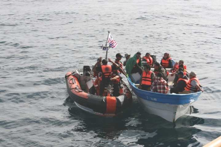 Crewmembers of the Coast Guard Cutter Petrel transfer suspected illegal immigrants from their disabled vessel to the Petrel's smallboat approximately 40 miles off the coast of San Diego, Oct. 1, 2010. The crew of the USS Boxer spotted the 16 people aboard waving their hands in distress and notified the Coast Guard, who transported them to U.S. Border Patrol personnel in Oceanside, Calif. U.S. Coast Guard photo