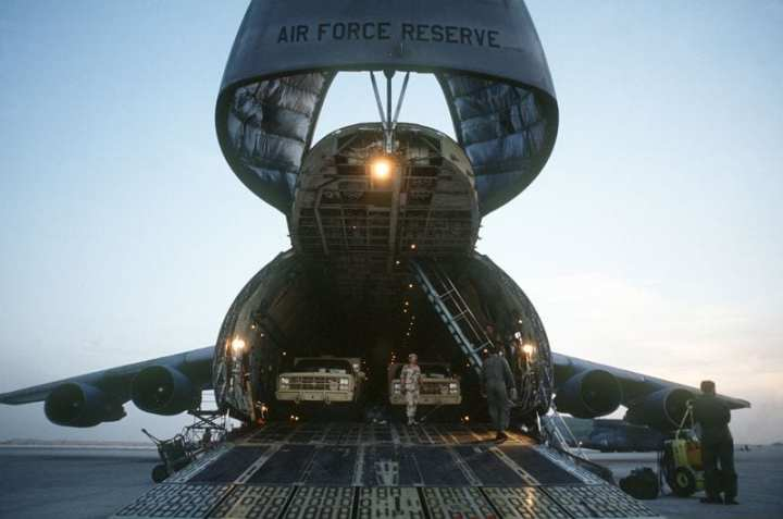 Military trucks are unloaded from the nose ramp of a C-5A Galaxy transport aircraft of the U.S. Air Force Reserve, Military Airlift Command, in support of Operation Desert Shield. DoD photo.