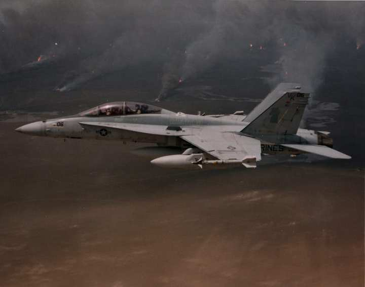 "A Marine Corps VMFA(AW)-121 ""Green Knights"" F/A-18D Night Attack Hornet flies over oil wells sabotaged by Saddam Hussein's forces as they retreated from Kuwait. The improved systems in the Hornet were a big step forward for the Marine Corps at the time. Photo courtesy of The Boeing Company."