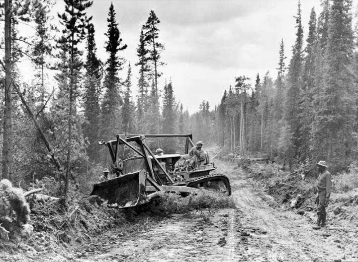 A tractor with grader widens the roadway of the Alcan Highway, ca. 1942. Library of Congress photo