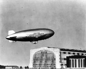 "A U.S. Navy ""K"" class blimp used for recruiting purposes flies over the airship hangar at Naval Air Station (NAS) Lakehurst, N.J., ca. 1955. As airships fell out of favor they became relegated to advertising duties. National Museum of Naval Aviation photo"