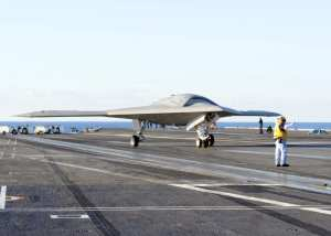 The X-47B demonstrator taxies on the Truman's flight deck. A crewmember with a remote control unit controls the aircraft under a flight deck controller's direction. U.S. Navy photo by Mass Communication Specialist 2nd Class David R. Finley Jr.