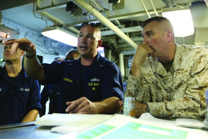 Lt. Gen. John Wissler, the U.S. Marine Corps' Deputy Commandant for Programs and Resources, listens to a brief by Lt. j.g. Joseph Kenworthy, aboard the amphibious assault ship USS Kearsarge (LHD 3), during visit to familiarize with amphibious assault capabilities. Kearsarge is underway providing surface orientation for Naval Reserve Officers Training Corps (NROTC) Midshipmen in support of Career Orientation Training for Midshipmen (CORTRAMID) East. U.S. Navy photo by Mass Communication Specialist 3rd Class Jonathan Vargas