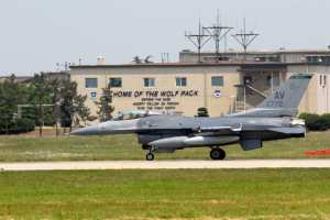 During an earlier deployment, an F-16 from the U.S. base at Aviano, Italy, taxies past an 8th Fighter Wing 'Wolfpack' building at Kunsan Air Base, Korea, emblazoned with the wing's three-point motto: 'Defend the base, accept follow-on forces and take the fight north.' U.S. Air Force photo