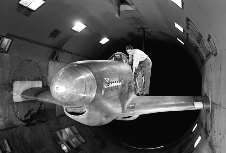 By testing a North American XP-51B Mustang with cropped wings in the 16-foot High-Speed Tunnel, Ames researchers traced the source of a serious rumble to the location of the plane's radiator cooling scoop below the fuselage. The problem scoop is barely visible below the wing. Lowering it slightly moved it outside the turbulent boundary layer and eliminated the rumble. Note the turntables in the walls for pitch adjustment. NASA image