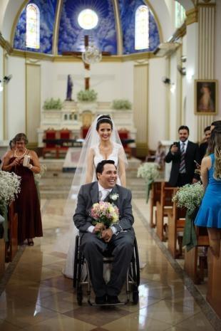Na saída da igreja, ela empurrava cadeira enquanto noivo segurava buquê. (Foto: Eurides Aoki)