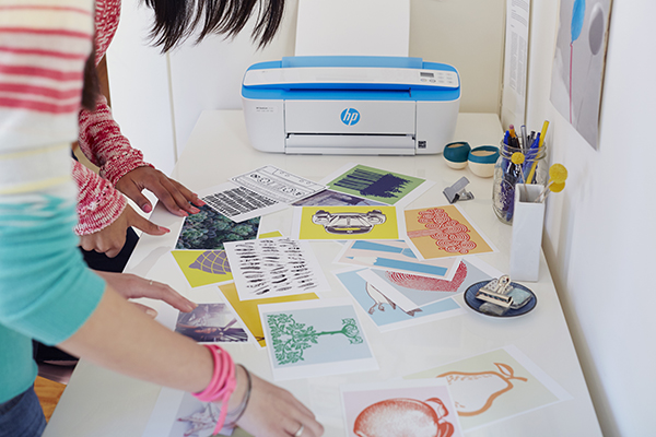 Two girls look through photographs and artwork printed on a HP DeskJet 3720 All-in-One.
