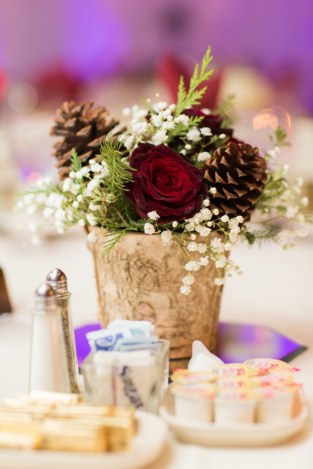 short red and green and white centerpiece with pine cones