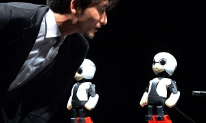 Japanese Tokyo University robot creator Tomotaka Takahashi chats with humanoid robot Kirobo (R) and back-up robot Mirata in Tokyo on June 26, 2013.  A small humanoid robot Kirobo which can talk will be sent into space to provide conversational company for a Japanese astronaut in the international space station on a six-month mission from this August.   AFP PHOTO / Yoshikazu TSUNO