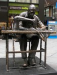scuplture of man sewing