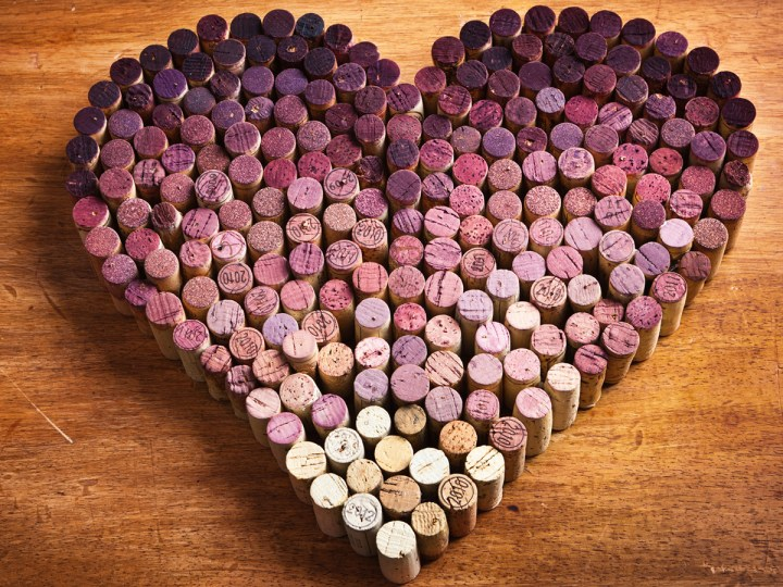 A large number of wine corks arranged to form the shape of a heart. The corks are arranged in a color pattern from the dark red gradually to the white wine corks. Concept photo for the passion and love of wine, and wine as a heart healthy drink. Photographed in horizontal format on a rustic wood background.