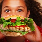 getty_rf_photo_of_tween_girl_eating_fast_food_chicken_sandwich
