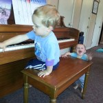 Nolan playing the piano while Evan cheers him on