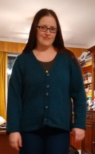 A woman stands smirking, modelling a freshly knit blue cardigan