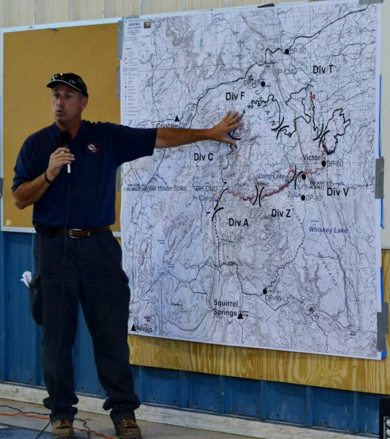 "Southwest Incident Management Team 3 Liaison Officer Ben Fish points out on the Assayii Lake Fire map where most of the fire containment exists, which is designated by black line instead of red lines around the fire's perimeter, during daily morning fire update at Tse Hootso Middle School ""Tin Building"" in Fort Defiance, Ariz. Photo by Marley Shebala. (Please credit when reusing photo.)"