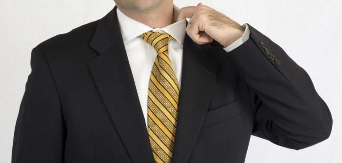 Businessman in black suit nervously adjusting collar