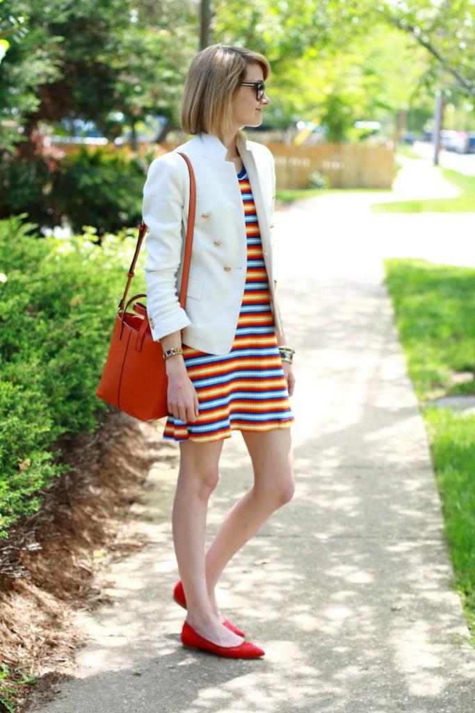 white blazer, orange bag, and striped dress