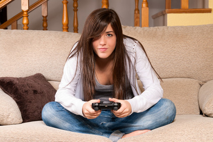 Young female concentrating playing videogames on sofa at home