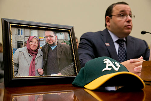 Ali Rezaian sits next to a photo showing his brother, Washington Post reporter Jason Rezaian, and their mother, during a House Committee on Foreign Affairs hearing for families with relatives jailed in Iran. (AP/Jacquelyn Martin)
