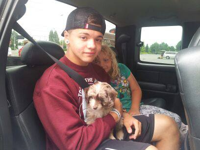 Our kids holding a mini Aussiedoodle puppy before she goes on the airplane to meet her new family